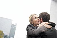 Couple embracing outdoors near buildings smiling