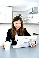 Businesswoman reading newspaper while having coffee
