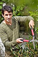 Man trimming plants with a hedge clippers