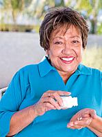 Senior Hispanic woman taking medication