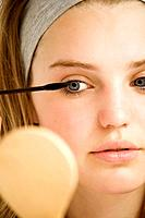 Girl applying mascara while looking at hand mirror