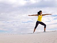 Mixed Race woman practicing yoga on sand dune