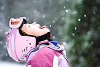 Asian girl sticking out tongue in snow
