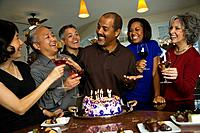 African man celebrating birthday with multi_ethnic friends