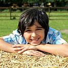 Boy lying on haystack, posing for the camera