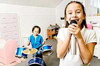 Asian sisters playing drums and singing