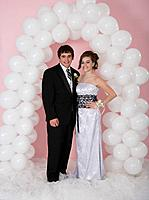 Hispanic couple under balloon arch at prom