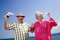 Senior couple on beach with badminton racquet and ball