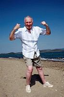 Male senior showing muscles on beach