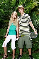 Boy and girl posing with badminton racquets
