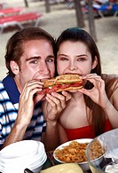 Young adult couple eating sandwich (thumbnail)