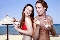 Young adult couple eating breakfast on beach (thumbnail)
