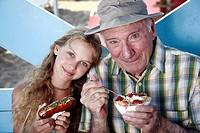Grandfather and granddaughter eating at beach