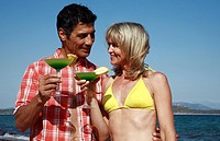 Mature adult couple with cocktails on beach