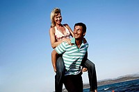 Mature adult couple piggyback on beach