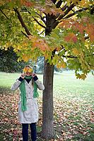 Woman covering eyes with maple leaves