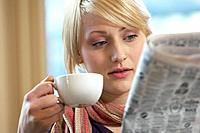 Woman drinking coffee and reading newspaper