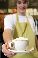 Barista serving cappuccino