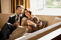 couple on couch holding glasses of wine