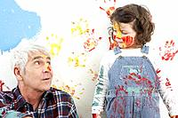 Grandfather and granddaughter covered in paint