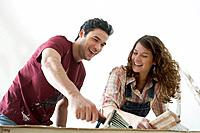 Couple preparing wallpaper strip