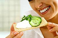 Young woman holding up cracker topped with cucumbers and cheese spread, cropped