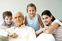Grandfather and three grandchildren, all smiling, portrait
