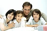 Family in front of birthday cake with lit candles, one boy wearing party hat