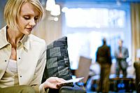 Woman Looking at Price Tag on Sofa
