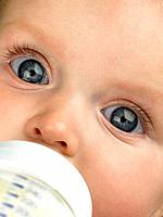 Baby's face close up with baby bottle
