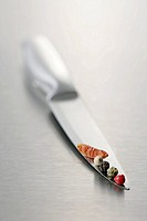 Peppercorns and chilli on a knife blade