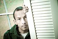 Hispanic man posing in front of a window