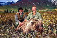 Two hunters pose with recently killed brown bear near Katmai in southwest Alaska