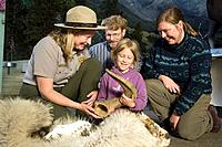 Female US Interpretive Ranger shows animal fur and horn to a visiting family at the visitor center Denali National Park Alaska