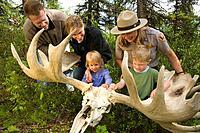 Female US Interpretive Ranger shows a moose antler and skull to a visiting family at the visitor center Denali NP Alaska