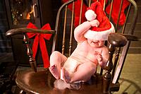 Infant girl in diaper wearing Santa Claus hat sitting in wooden rocking chair looking at camera winter Alaska