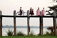 Buddhist monks and nuns on the U Bein bridge in teak wood in the old royal city of Amarapura near Mandalay, Myanmar