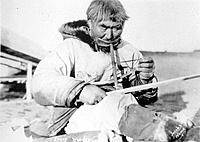Historical image of a native man using a bow drill to work on ivory Nome WE Alaska