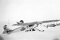 Historical image of a plane on skis belonging to Wien Alaska Airways Inc parked near the beach in Nome Winter Nome WE Alaska