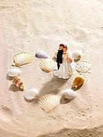 Seashells in shape of heart with bride and groom figurines