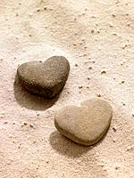 Heart shaped stones in sand