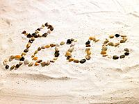 Love written with stones in sand