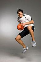 Young man holding basketball in midair, studio shot
