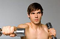 Young man working with dumbbells, studio shot