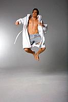 Mid adult man in bathrobe jumping in air