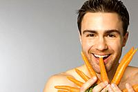 Close_up of young man eating carrots