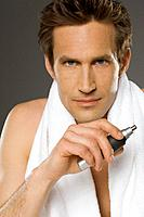 Mid adult man holding nose hair trimmer, portrait (thumbnail)