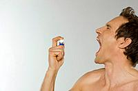 Mid adult man spraying breath freshener