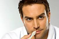 Close-up of man using lip balm (thumbnail)