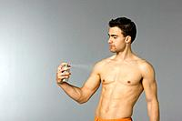 Young man spraying body deodorant